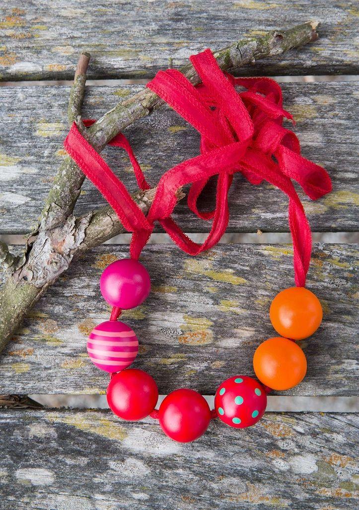 Un fabuleux bijou fait d'une lanière en soie colorée avec perles en bois peintes. Ajustez la longueur en le nouant plus ou moins haut. Une vraie merveille pour toutes les occasions!