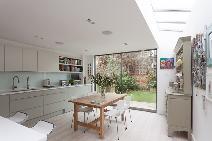 Extension to a period home in Putney. Open plan kitchen dining looking out to the garden and a strip of roof lights that bring light deep into the plan.