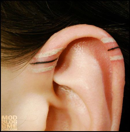 something different...striped ear tattoo .  unknown artist