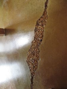 Creating cracks and filling with... rocks, cork, glass, etc., seal with epoxy, then stain concrete, or vise versa.