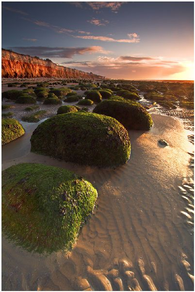 """North of the modern town centre in Old Hunstanton find the gorgeous banded cliffs are made of layers of red limestone with a white chalk layer on top. The cliffs – a perfect geology textbook illustration – are framed by a foreground of chalky sand and green, seaweed-covered rocks. With the setting sun lighting up the cliffs as it lowers across the Wash, this is the sort of place that landscape photographers get excited about."" Slow Travel Norfolk; www.bradtguides.com"