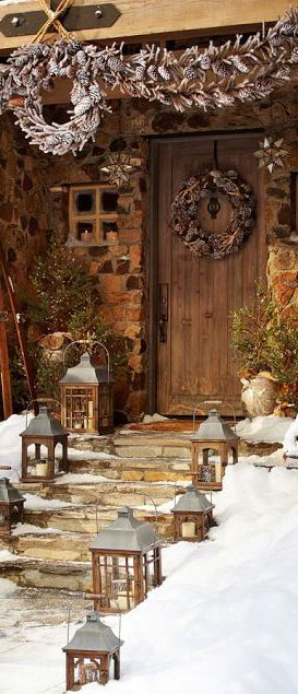 A collection of rustic lanterns and pine cone boughs make an elegant entry.