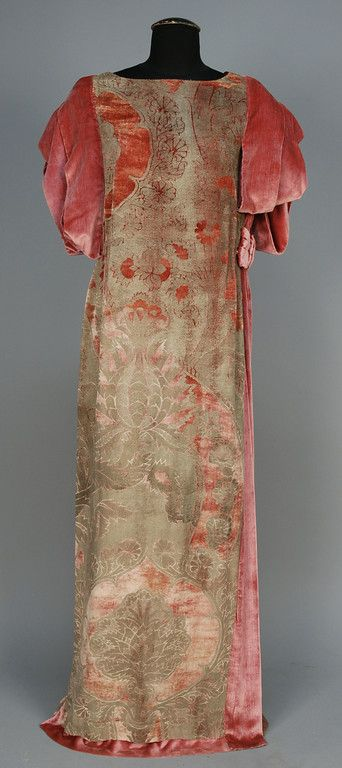 ITALIAN STENCILED VELVET GOWN, 1920s. Dusty rose silk with asymmetrical stylized silver floral having short sleeve comprised of wide velvet bands and left side insert with ruching at waist with bow detail, neckline bound in metallic thread. B-38, L-57. Excellent.