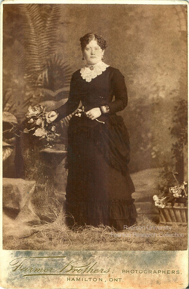Woman standing. Photographed by the Farmer Brothers of Hamilton. Elaborate decorative logo on reverse. FRC 2002.04.284
