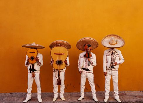 Four mariachis hiding behind instruments. Start the celebration early...in honor of your day.