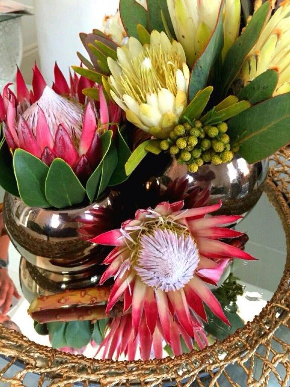 Red and white #proteas in #coppervases on a gold framed rattan mirror for a corporate function as Guest table centre pieces #functionsforafrica...