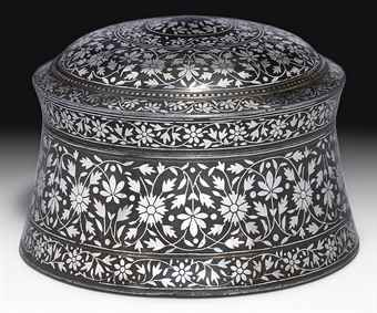 A BIDRI PANDAN   PROBABLY BIDAR, DECCAN, SECOND HALF 17TH CENTURY   Of waisted cylindrical form with separate domed cover, the body decorated with a main band of silver-inlaid flowerheads issuing interlacing floral vine, a minor band of meandering floral vine below, the cover similarly decorated with bands of similar floral meander, most inlay surviving