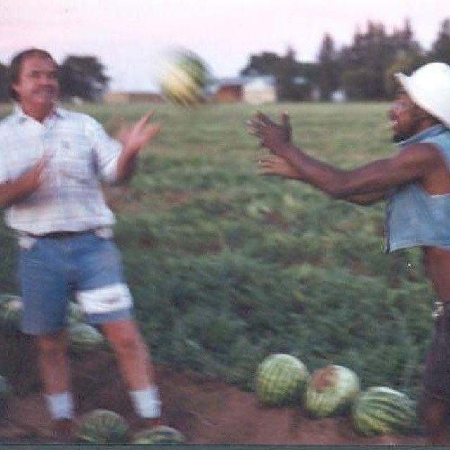 Hartswater, Zuid-Afrika, december 2003. Rond 6 uur 's avonds en nogal schemerig. Uit de hand genomen met met mijn oude Leica R5. Sluitertijd 1/30 sec. voor zover ik me herinner.  Hieronder twee beschrijvingen die ik bij deze foto maakte. Welke tekst spreekt je het meest aan? (1) Een boer en een van zijn werkers gooien met  een 'waatlemoen'. De boer heet Fanie Boshoff, hij speelt met 'Spyker' en ze hebben duidelijk plezier.  December 2003, Hartswater, Zuid-Afrika. Het is een foto van een land…