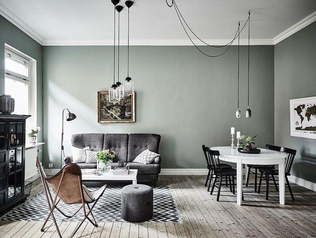J'invite ma salle à manger au salon : canapé en tissu gris et fauteuil en cuir répondent à la table blanc laqué