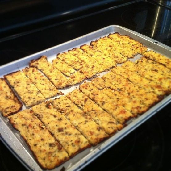 """(Primal) Cauliflower Cheese Sticks 1/2 of a head of a large cauliflower """"riced"""" (use your cheese grater) 1 tsp extra light olive oil 2 cloves garlic, minced 1 large egg white, lightly beaten 1/2 cup mozzarella cheese (we used light string cheese and pulled it apart….it's all I had) 1/2 tsp dried Italian herb seasoning"""