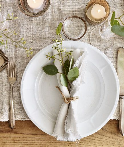 Nestle a bit of seeded eucalyptus in a loosely rolled raw-edge napkin (an earthy color is nice) and wrap twice with twine. A sprig of evergreen works just as beautifully. Stick with neutrals for the dishes and other table accents to keep the look natural and organic.