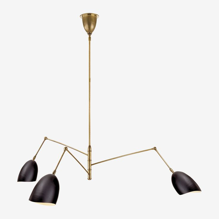 The Sommerard Triple Arm Chandelier in Hand-Rubbed Antique Brass with Black by AERIN • A retro-inspired piece by AERIN, the Sommerard Triple Arm Chandelier with its sleek shades and moveable triple arms allow you to focus light wherever you need it most. Each arm is adjustable and can also be angled.
