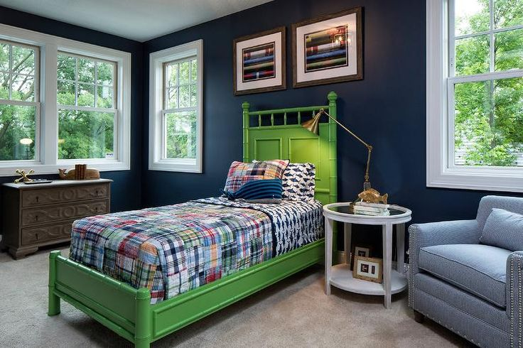 Walls painted in Benjamin Moore Newport Blue frame a blue and green boys bedroom featuring a green bamboo bed dressed in patchwork bedding accented with a matching pillow, a blues striped whale pillow, and a white and blue fish print shams.