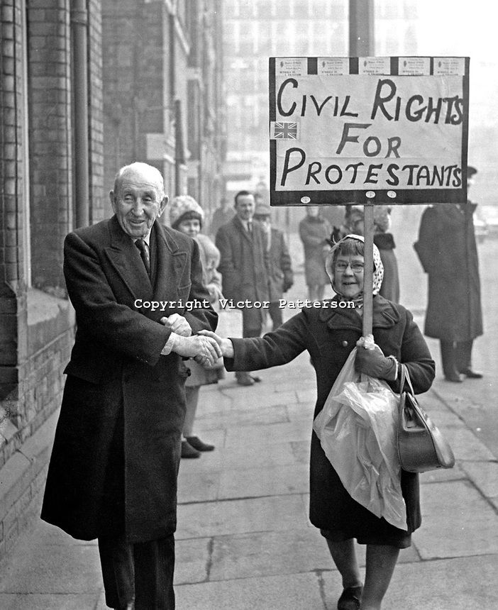 Lord Brookeborought, 1st Viscount, previously known as Sir Basil Brooke, former Prime MInister of N Ireland, arriving at the Ulster Unionist Party's headquarters in Glengall Street, Belfast, N Ireland, shakes hands with a placard-carrying supporter of the Rev Ian Paisley. The legend on the placard was Civil Rights for Protestants. The purpose of the Unionist Party meeting was to give members the opportunity to support a vote of confidence in Prime Minister, Captain Terence O'Neill. ...