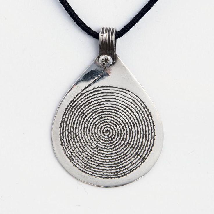 ***Pandantiv spirală Waza, lucrat manual în Niger. Spirala, simbol al evoluției spirituale în multe culturi, este gravată cu o precizie extraordinară de un bijutier tuareg. Pandantivul se vinde împreună cu un șnur negru la baza gâtului.