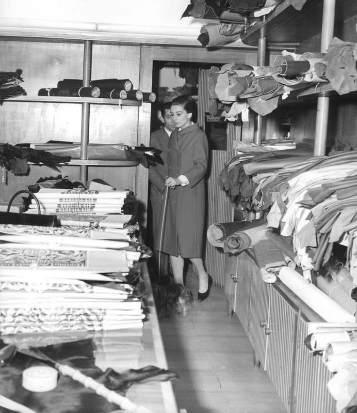 The actress Audrey Hepburn photographed with Mr. Famous (her Yorkshire Terrier) by Elio Sorci during her shopping at a store on Via Crispi in Rome (Italy), in January 1960. Audrey was wearing: • Coat: Givenchy (of red wool, double-breasted with...