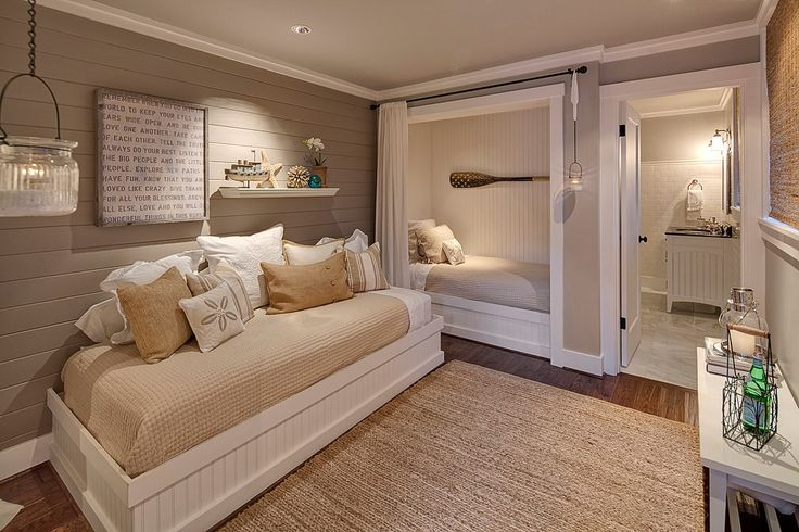 Earthy colors, neutral accents and plank wall treatments make for a cozy bunk room in this coastal home.