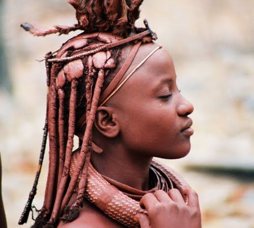 Himba People, Namibia, Africa:  The Himba wear little clothing, but the women are famous for covering themselves with otjize, a mixture of butter fat and ochre, possibly to protect themselves from the sun. The mixture gives their skins a reddish tinge. This symbolizes earth's rich red color and the blood that symbolizes life, and is consistent with the Himba ideal of beauty. Women braid each other's hair that they extend with plastic hair, and cover it except the ends, in their ochre…