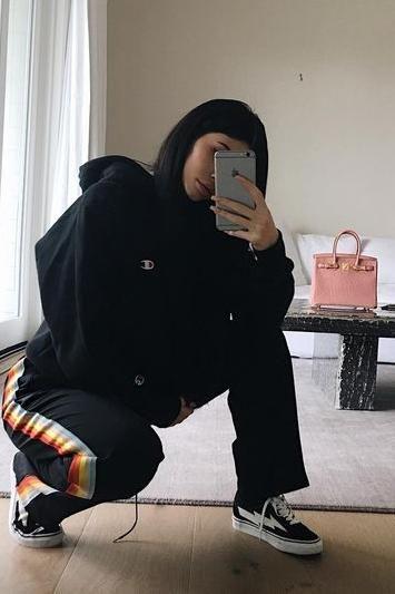 Kylie Jenner wearing Revenge x Storm Vans, Hermes Birkin Bag, Champion Reverse Weave Hoodie Sweatshirt and Chloe Rainbow Stripe Cady Track Pants