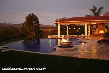 Vanishing edge swimming pool with spa and fire & water features, adjacent to custom outdoor fireplace