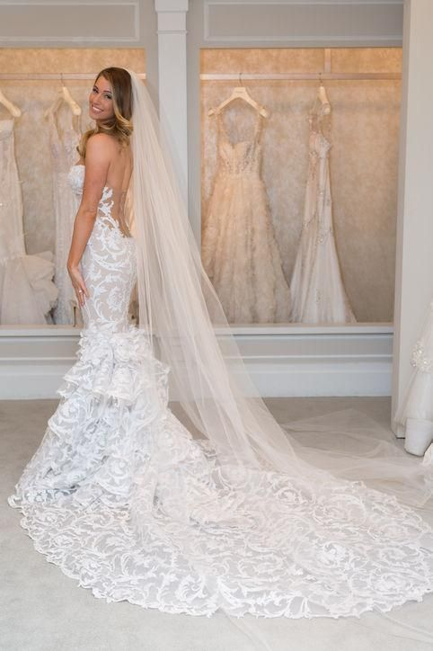 Lots of lace and a super low-cut open back makes this Pnina Tornai wedding dress extra breathtaking (and the long veil doesn't hurt either)