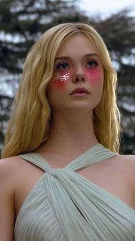 Elle Fanning wears a dramatic beauty look with pink under eyeshadow and lots of glitter framed by her long, golden hair.