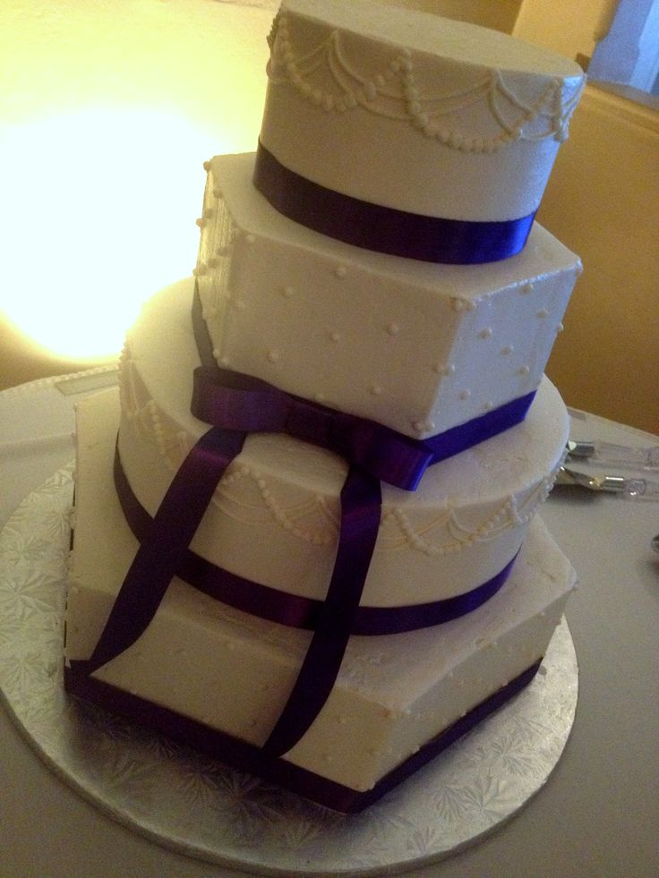 A mix of hexagon and round tiers with purple satin bands.