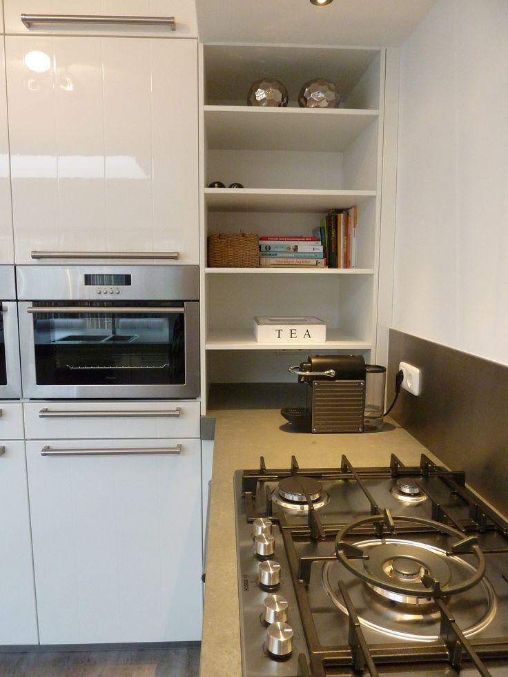 Heerlijke werkhoogte bij de oven en magnetron. Ook de loze hoek is optimaal benut door het werkblad mooi door te laten lopen en met planken voor bv kookboeken.