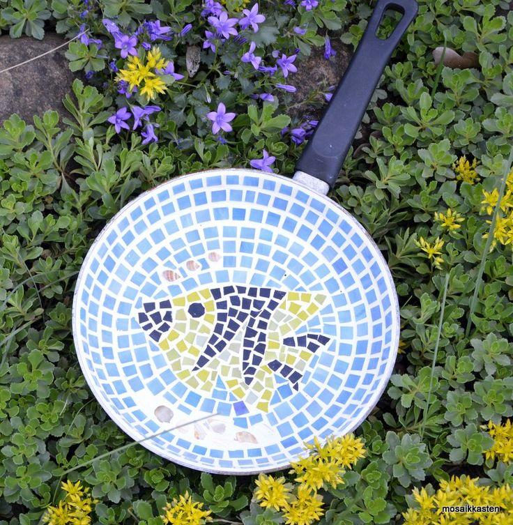 Die Vogeltränke wurde aus einer alten Pfanne gefertigt, die dementsprechend Gebrauchsspuren aufweist. Blaues, gelbes und schwarzes Tiffanyglas ist mit der