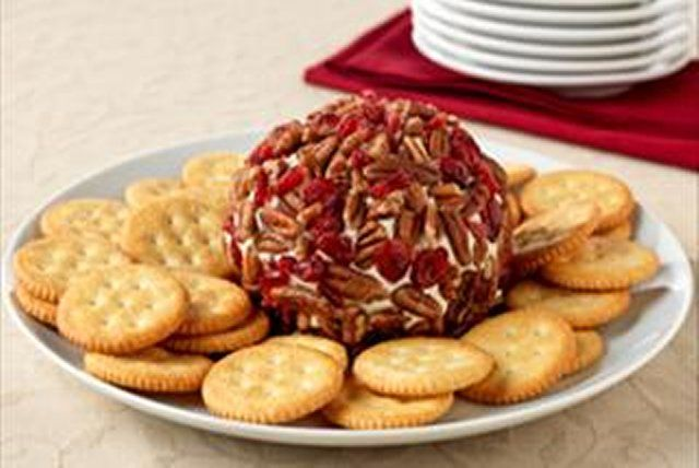 Classic ROKA Cheese Ball 1 pkg. (8 oz.) PHILADELPHIA Cream Cheese, softened 1 jar (5 oz.) KRAFT ROKA Blue Spread 1/2 tsp. garlic powder 3/4 cup chopped PLANTERS Pecans 1/4 cup dried cranberries RITZ Crackers  Mix first 3 ingredients until well blended. Refrigerate 2 hours. Shape into ball; coat with remaining ingredients.