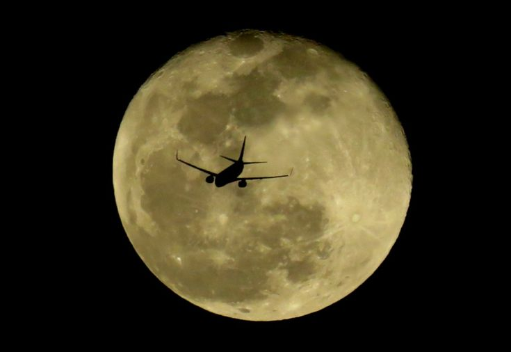 A plane on a background of the full moon. Space is closer than it seems.