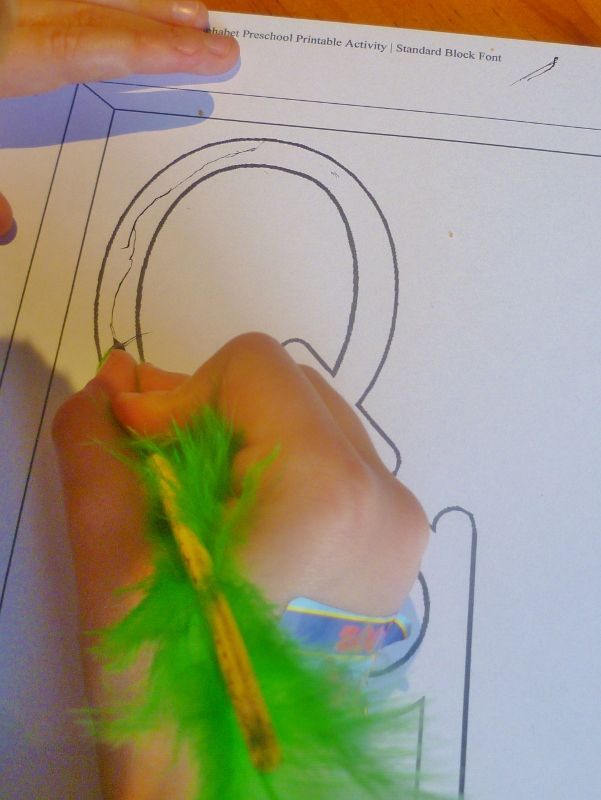Make the letter Q using a quill and ink