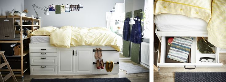 A bed made from kitchen cabinets with a yellow quilt in a small room. A bedside drawer pulled out with a book and glasses inside.