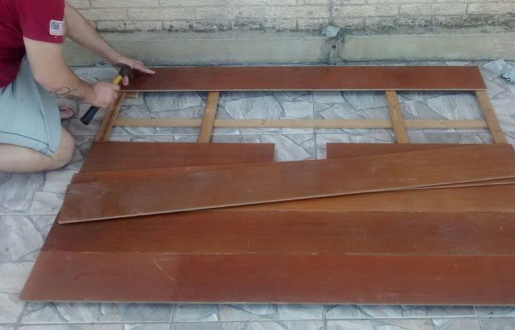 Achamos no lixo, placas de piso de madeira e levamos para casa. Cortamos na largura do rack 1,60 cm. Nessa foto meu marido está fixando as placas nas ripas de madeira que erma um estrado velho de cama.
