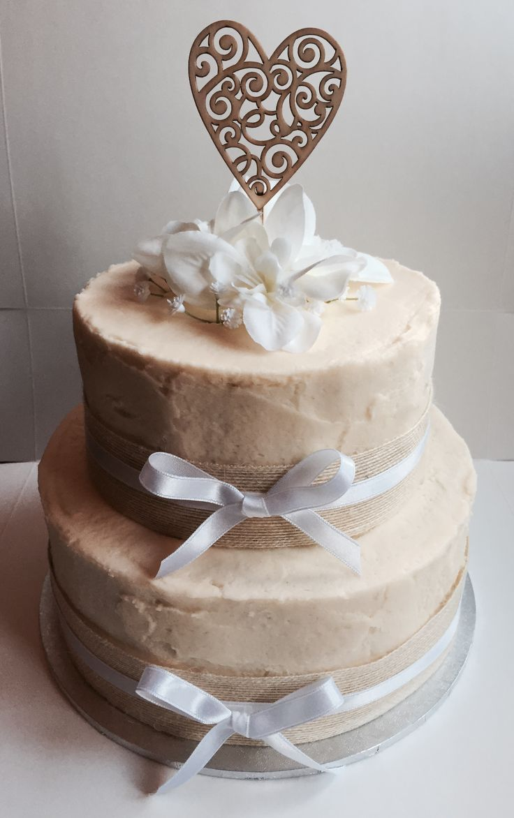 Rustic wedding or engagement cake with hessian ribbon and wooden heart topper.