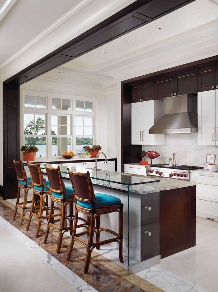 """In this kitchen, a clear glass bar """"floats"""" above the island, providing seating for four using PierceMartin barstools with chair cushions in a Boussac fabric."""