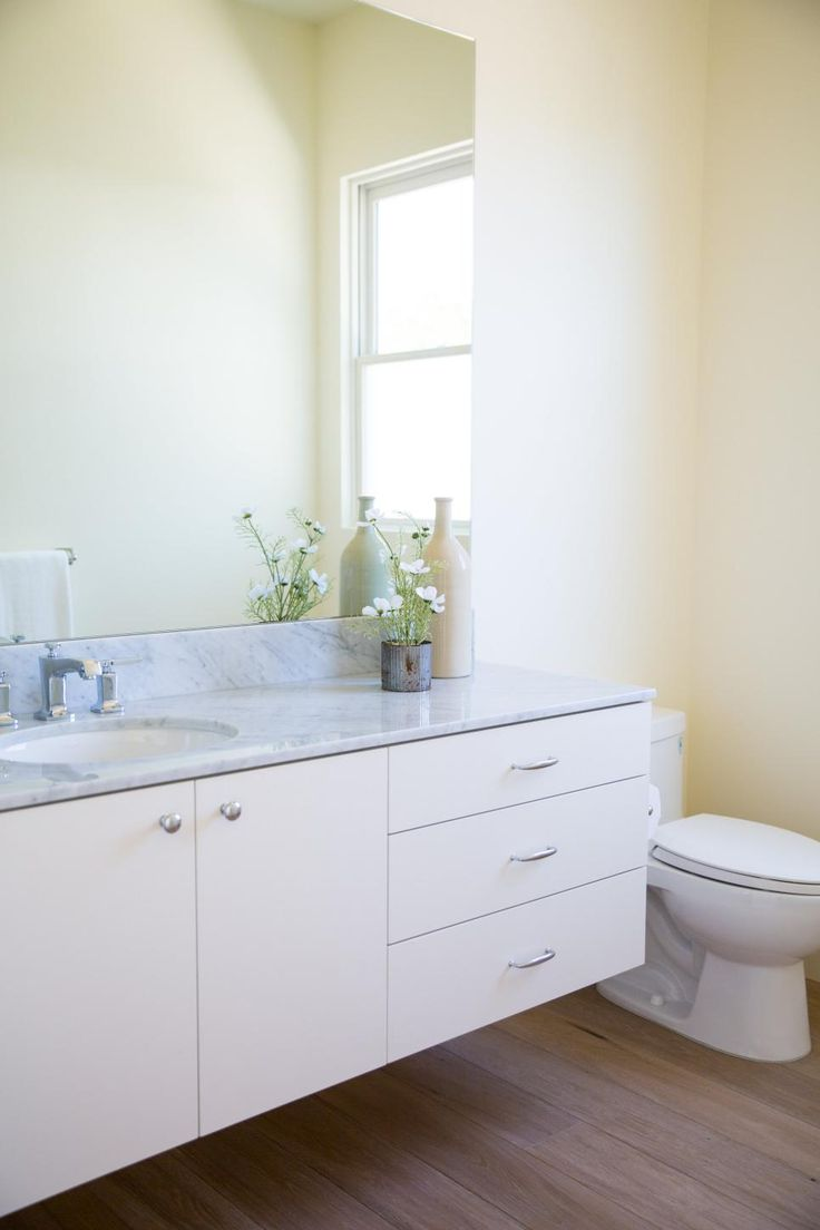 Simple and efficient: A white-and-neutral bathroom like this can't help but look clean and bright. The large, frameless mirror adds to this sense of openness. Outstanding elements in the space include the gorgeous Carrera marble counter, floating vanity and pale, wide-plank wood floors.
