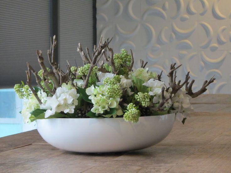 Stoere hoogglans witte schaal gevuld met hortensia's, hout en bessentakken