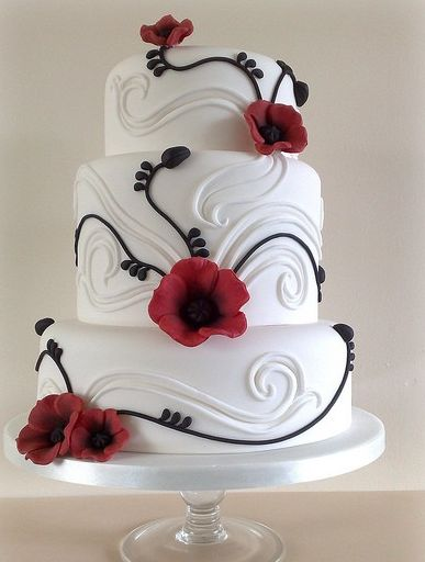 white wedding cake with black details and red flowers