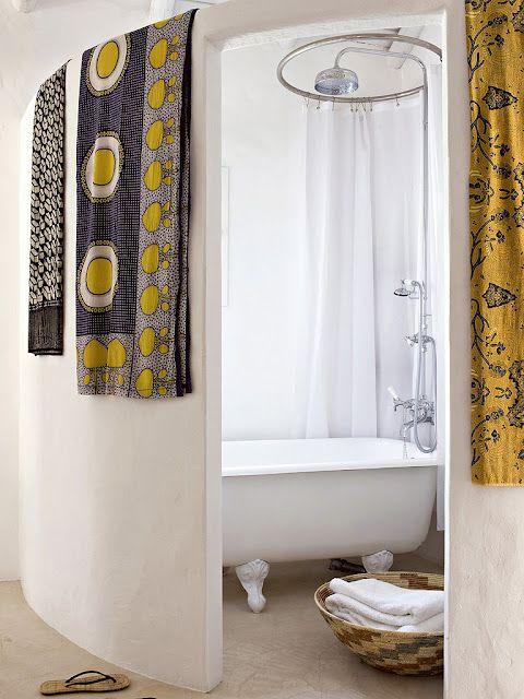 Harmonie des jaunes et noirs de ces tissus pendus, pour donner du relief à une salle de bains blanche.