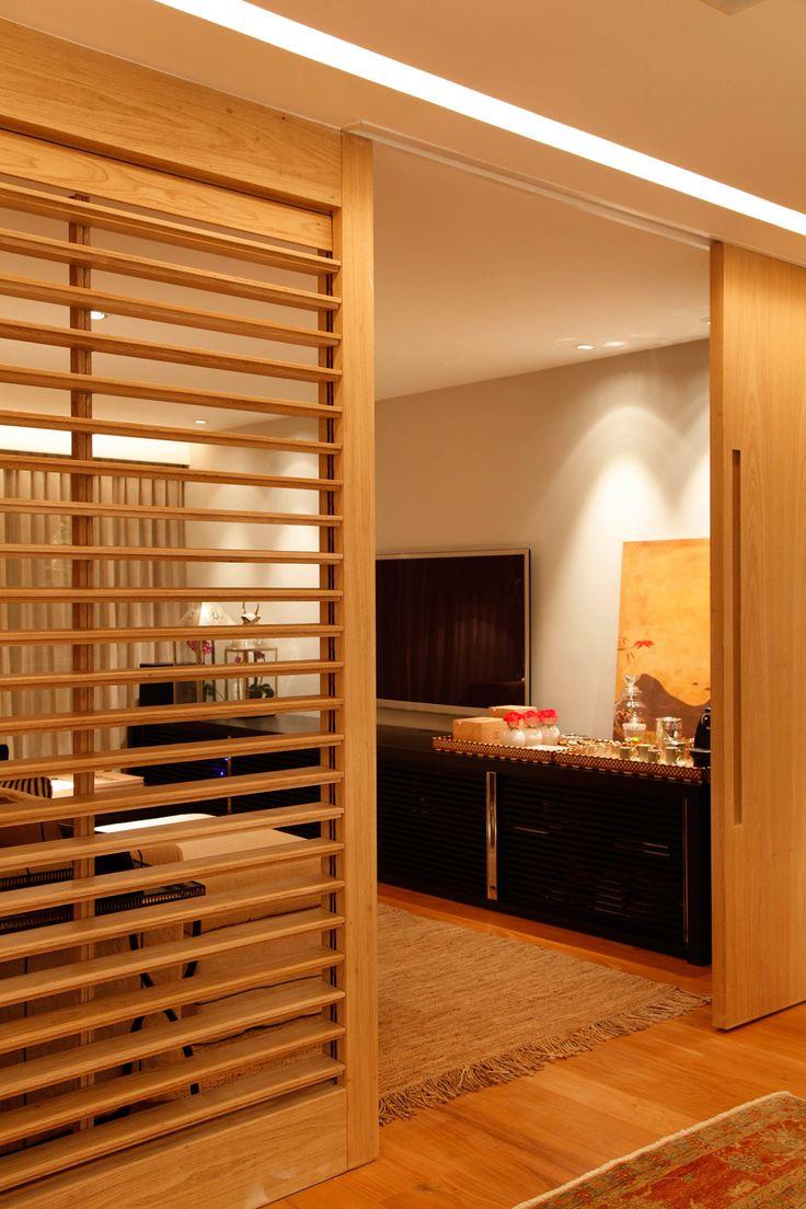 Porta e painel ripado em madeira, que divide mas ainda permite uma conexão entre os ambientes!