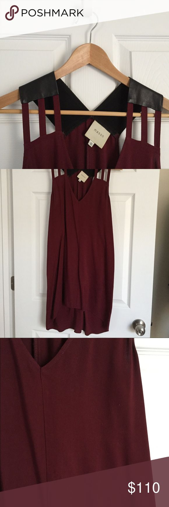 """Modern Dress with Real Leather Accents Rich burgundy shift dress with unique leather shoulder detail and cutouts. Hi-lo skirt, but the effect is minimal. Front hem hits just above the knee on a 5'7"""" frame. Fits up to a size 4. Slips on. By Mason, from Anthropologie.   NOTE: This dress is not vegan. The leather on the shoulders is 100% lambskin (see tag photo). Mason Dresses High Low"""