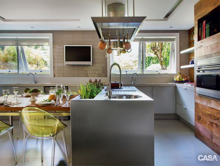 Nesta casa carioca, a cozinha do dia a dia fica num anexo do jardim. Já o ambiente interno, de 28 m², foi planejado para conter todos os equipamentos. A ilha de silestone.com ganhou um recorte de 1,80 m de extensão. Na parede da TV, as pastilhas de vidro na cor fendi medem 10 x 3 cm (Vitrica). O projeto de iluminação é da Lumini. A profissional concebeu uma circulação generosa em torno da ilha, na qual instalou o cooktop e fez um rasgo no tampo, que acomoda utensílios e vasos de ervas.