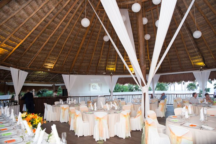 The inside of the #Palapa was mostly #white but Sara and Brant were sure to maintain their #neon color theme by adding #limegreen and #orange accents around the room | Photography courtesy of Willow Lane Photography #neonwedding #destinationwedding #colorful #vibrant #mexico #grandsirenis