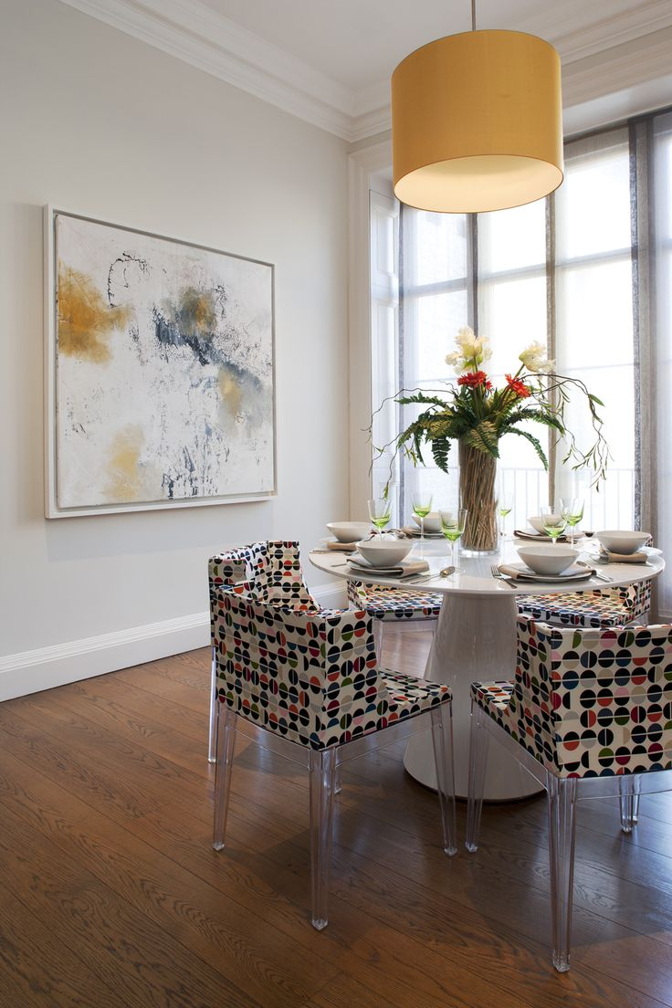 The contemporary dining area is a creative mix of bright colours underpinned by simplicity. The wooden flooring acts as a blank canvas for the lively coloured chairs which is offset by the clean circular dining table. The wall art features a splash of colour blending well with the orange chandelier and the greenery at the centre of the table.  #dining #diningarea #diningtable #lamps #wallart #woodenflooring #plants