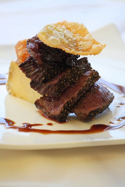 Peppercorn encrusted ostrich tenderloin with saint andres cheese, aged balsamic, and hazlenut crusted wonton chip
