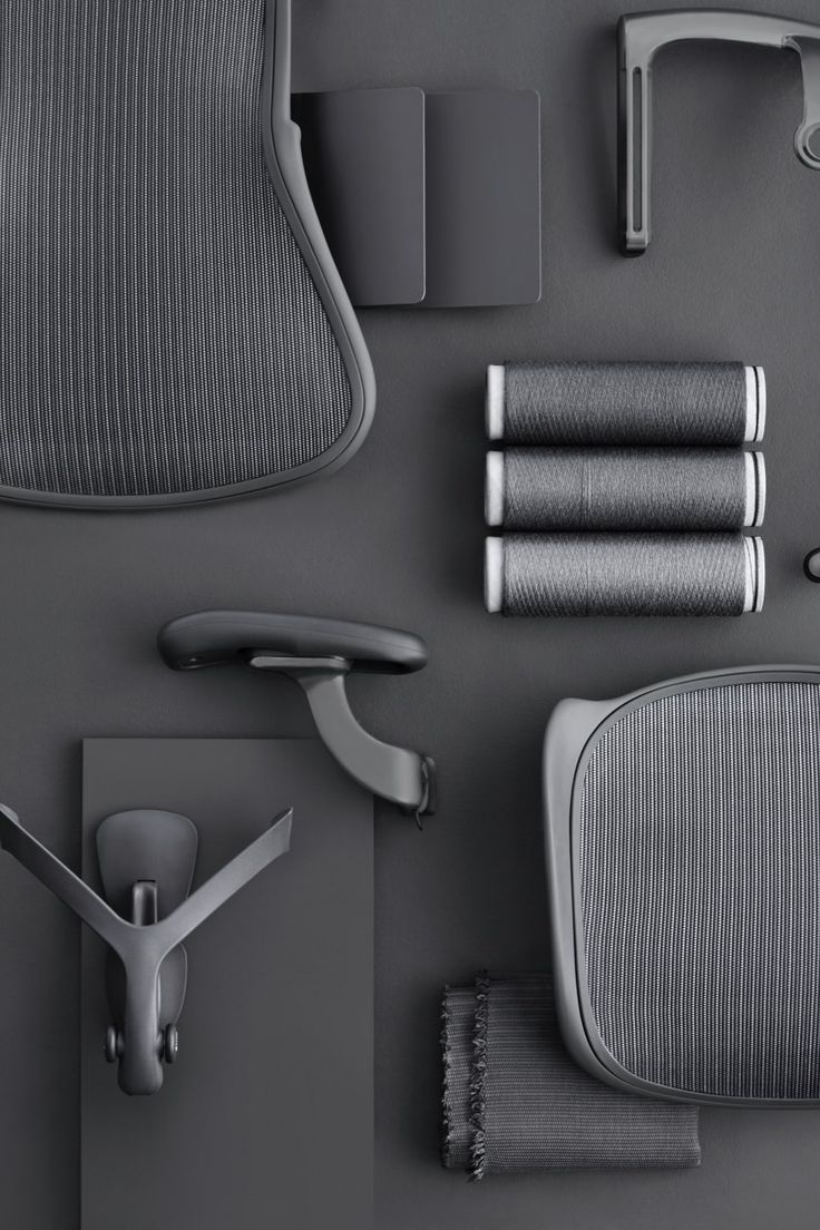Individual parts of the new Aeron chair; including PostureFit SL pads, an armrest, set, and spools of Pellicle thread—all in Carbon finish—rest on a grey surface