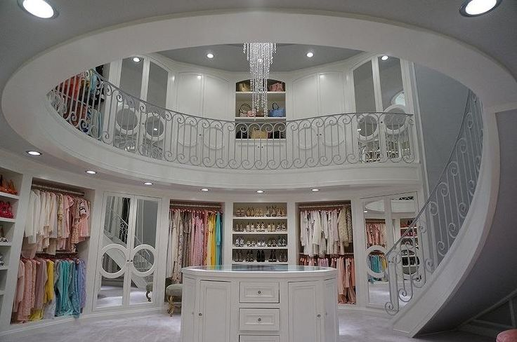 Amazing two story closet features a spiral staircase leading up the second floor fitted with mirrored closet doors and shelves lined with designer bags.