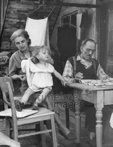 Familie in München, 1957 helmut37/Timeline Images #Fürsorge #1950er #1950ies #Zeitung #Mann #Vater #Frau #Mutter #Kind #Mädchen #Eltern #München #historisch #historical #Familienfoto #schwarzweiß