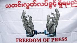 Journalists hold a banner as they protest against a law they say curbs free speech, at the start of a trial of two journalists who the army is suing for defamation over a satirical article, in Yangon